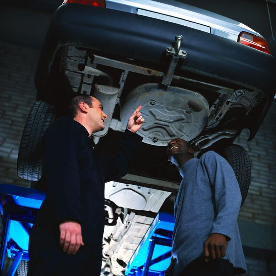 portrait of a young man standing below the undercarriage of his car with a mechanic