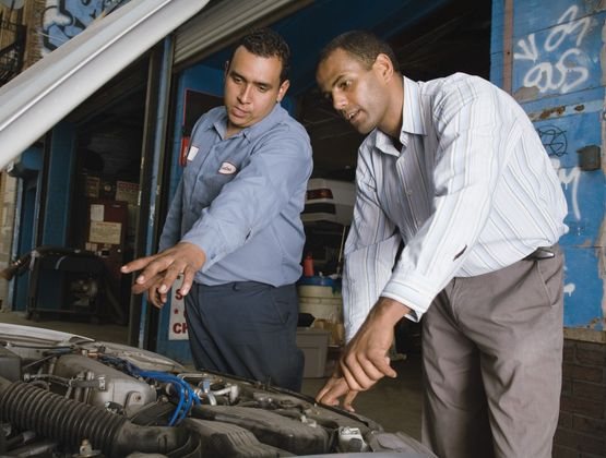 Mechanic and customer looking at engine